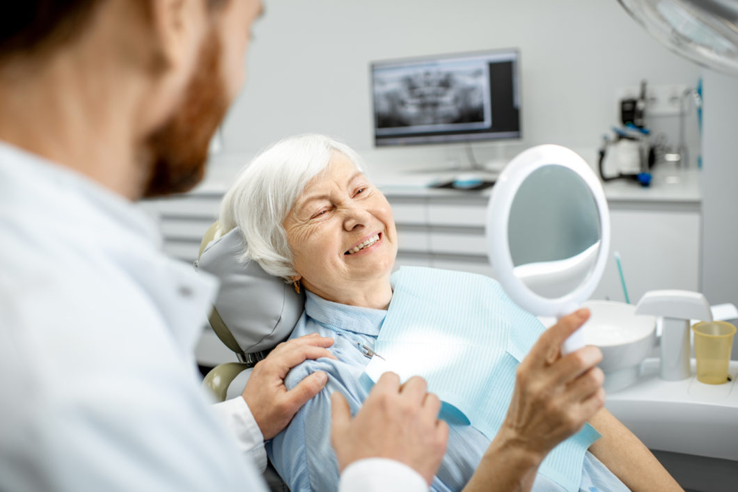 Happy elderly patient with mirror